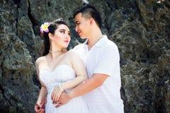 Jeunes mariés asiatiques sur une plage tropicale Mariage et lune de miel Photographie stock libre de droits