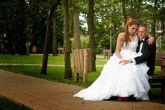 Jeunes mariés assis en parc photographie stock