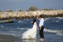 Jeunes mariés au bord de la mer Photographie stock libre de droits