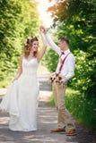Jeunes mariés au jour du mariage marchant dehors Photographie stock libre de droits