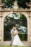 Jeunes mariés au jour du mariage marchant dehors sur la nature de ressort Couples nuptiales, femme heureuse de nouveaux mariés et Image libre de droits