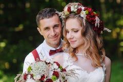 Jeunes mariés au jour du mariage marchant dehors sur le parc de ressort photo libre de droits