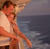 Jeunes-mariés au rail de bateaux au coucher du soleil appréciant le sillage Images libres de droits