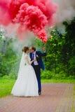 Jeunes mariés avec de la fumée colorée de rouge Photographie stock