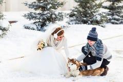 Jeunes mariés avec des chiens de traîneau de chien en hiver photos stock
