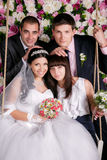 Jeunes mariés avec des demoiselles d'honneur et des garçons d'honneur à l'arrière-plan de studio des fleurs Photographie stock libre de droits