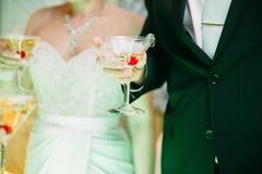 Jeunes mariés avec des verres de champagne dans sa main Images libres de droits