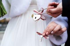 Jeunes mariés avec le cadenas de l'amour avec des clés Photo stock