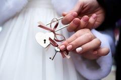 Jeunes mariés avec le cadenas de l'amour avec des clés Images libres de droits