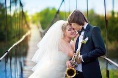 Jeunes mariés avec le saxo image stock