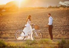 Jeunes mariés avec un vélo blanc de mariage photographie stock