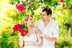 Jeunes mariés blonds heureux ayant l'amusement sur un jardin tropical wed photos stock