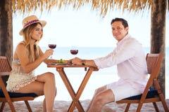 Jeunes-mariés buvant du vin à la plage Images stock