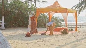 Jeunes mariés Bypass Purifying Fire à l'auvent sur la plage banque de vidéos