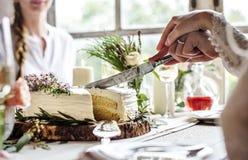 Jeunes mariés Cutting Cake sur la réception de mariage Photographie stock