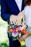 Jeunes mariés démontrant des anneaux sur leurs mains contre le bouquet de fleur comme fond Photographie stock libre de droits
