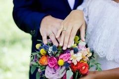 Jeunes mariés démontrant des anneaux sur leurs mains contre le bouquet de fleur comme fond Photo stock