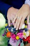 Jeunes mariés démontrant des anneaux sur leurs mains contre le bouquet de fleur comme fond Images stock
