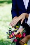Jeunes mariés démontrant des anneaux sur leurs mains contre le bouquet de fleur comme fond Photos libres de droits