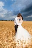 Jeunes mariés d'Inlove dans le domaine de blé avec le ciel dramatique au b Images libres de droits