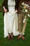 Jeunes mariés dans des chaussures de brun d'automne sur l'herbe, montrant des jambes, épousant le concept photo stock