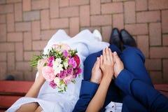 Jeunes mariés dans des vêtements lumineux sur le banc Photo stock