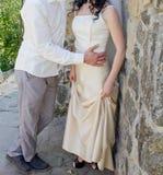 Jeunes mariés dans l'amour au mur en pierre Photos stock