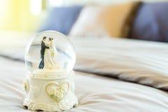 Jeunes mariés dans la boule en verre sur le lit Photo libre de droits