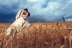 Jeunes mariés dans le domaine de blé avec le ciel dramatique Image stock