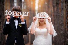 Jeunes mariés dans les bois avec une inscription dans les mains Photographie stock