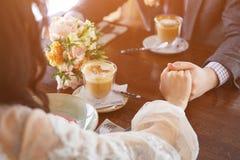 Jeunes mariés dans un restaurant luxueux tenant des mains et buvant une tasse de latte de café photos stock