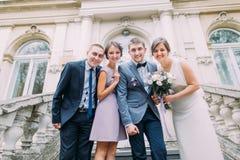 Jeunes mariés de nouveaux mariés avec le garçon d'honneur heureux plus la demoiselle d'honneur posant aux escaliers du bâtiment c Image stock