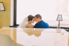 Jeunes mariés de nouveaux mariés près du piano à queue blanc allant embrasser Fenêtre lumineuse sur le fond Photo stock