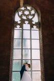 Jeunes mariés de nouveaux mariés se tenant devant la vieille cathédrale gothique arquée de fenêtre Photo stock
