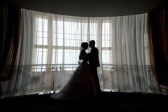Jeunes mariés de silhouette embrassant devant la fenêtre étroite Images stock