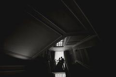 Jeunes mariés de silhouette embrassant devant la fenêtre étroite Photographie stock