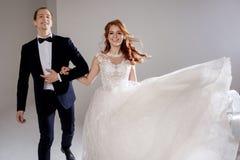 Jeunes mariés drôles et heureux, danse et saut avec bonheur, marié Portrait de studio, fond clair Image libre de droits
