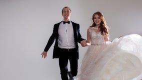 Jeunes mariés drôles et heureux, danse et saut avec bonheur, marié Portrait de studio, fond clair Photo libre de droits