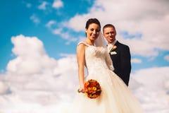Jeunes mariés drôles sur le fond de nuages Images libres de droits