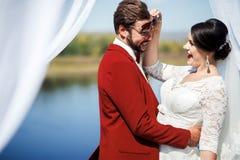 Jeunes mariés dupant autour à la séance photos après cérémonie, voûte intérieure avec le tissu blanc de tissus Couleur de mariage Image libre de droits