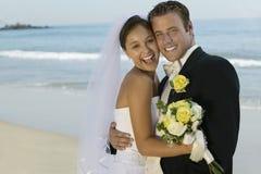 Jeunes mariés Embracing On Beach photo libre de droits