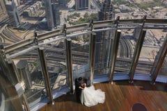 Jeunes mariés embrassant au-dessus du paysage urbain de Dubaï Image libre de droits