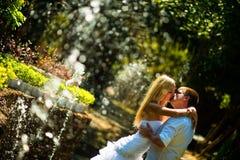 Jeunes mariés embrassant au milieu du jet Images libres de droits