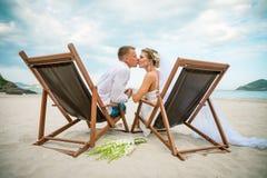 Jeunes mariés embrassant dans la chaise longue par la mer leur jour du mariage photographie stock
