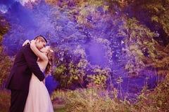 Jeunes mariés embrassant dans la forêt avec de la fumée pourpre Photo stock