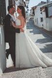 Jeunes mariés embrassant dans la rue photo stock