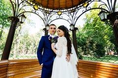 Jeunes mariés embrassant dans la tonnelle Couples de mariage dans l'amour au jour du mariage Photo libre de droits