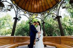Jeunes mariés embrassant dans la tonnelle Couples de mariage dans l'amour au jour du mariage Photos libres de droits
