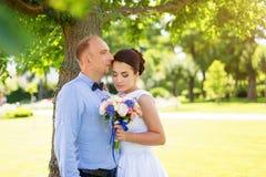 Jeunes mariés embrassant dehors Jour du mariage des couples, de la femme heureuse de nouveaux mariés et de l'homme nuptiales embr Photos stock