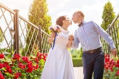 Jeunes mariés embrassant dehors Jour du mariage des couples, de la femme heureuse de nouveaux mariés et de l'homme nuptiales embr Photo stock